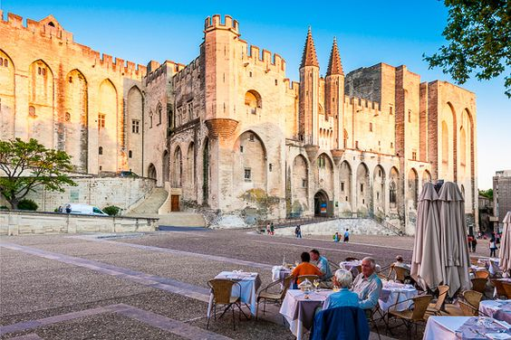AVIGNON - SEPTEMBER 9: Pope palace in Avignon. Central square with people sitting in front of the palace in the cafe. September 9, Provence, Alps, Cote d'Azur, France, Europe.